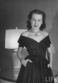 Frances Bergen in off-the-shoulder dress, wearing charm around her neck and several charm bracelets.